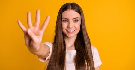 Frau zeigt die Zahl vier mit den Fingern